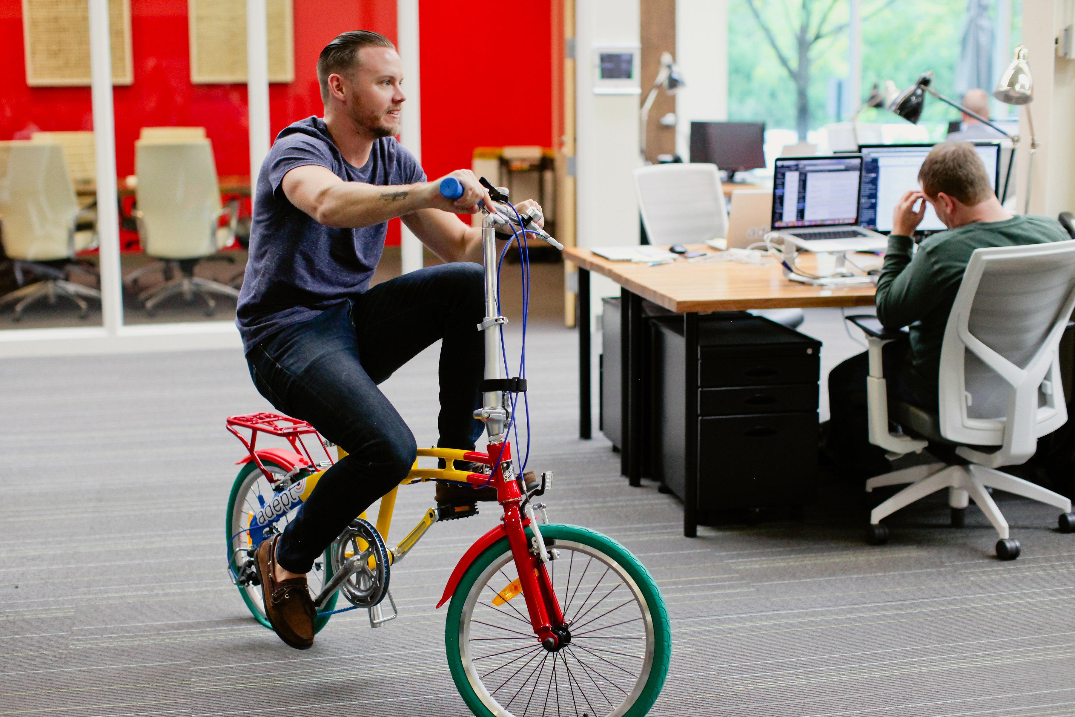 samuel riding google bike in adept office